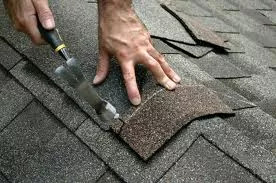 Pitcure of person nailing roofing tiles to roof
